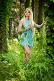 Recht junges blondes Mädchen mit dem langen Haar im Türkiskleid Stockfotos