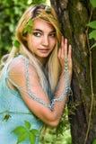 Recht junges blondes Mädchen mit dem langen Haar im Türkiskleid, das im grünen Wald steht Stockbild