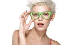 Recht junges blondes Modell, das kühle Brillen trägt Stockbild