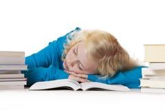 Recht junges blondes Schulmädchen schläft auf Lehrbuch Stockbilder