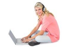 Recht junges blondes Sitzen unter Verwendung des Laptops, der Musik hört Lizenzfreie Stockfotografie