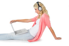 Recht junges blondes Sitzen unter Verwendung des Laptops, der Musik hört Stockfotografie