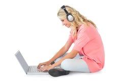 Recht junges blondes Sitzen unter Verwendung des Laptops, der Musik hört Lizenzfreies Stockfoto