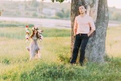 Recht junges blondes tragendes lila Kleid und Kranz, die im Schwingen während ihr hübscher Freund steht nahen Baum sitzt Lizenzfreie Stockbilder