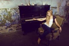 Recht junges blondes wirkliches Mädchen am Klavier verrosteten Innenraum im im alten Stil, Weinlesekonzept Stockfoto