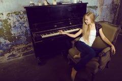 Recht junges blondes wirkliches Mädchen am Klavier verrosteten Innenraum im im alten Stil, Weinlesekonzept Stockfotografie