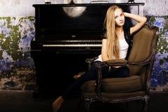 Recht junges blondes wirkliches Mädchen am Klavier verrosteten interi im im alten Stil Stockfotos