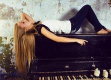 Recht junges blondes wirkliches Mädchen am Klavier verrosteten interi im im alten Stil Lizenzfreie Stockfotografie