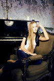 Recht junges blondes wirkliches Mädchen am Klavier verrosteten interi im im alten Stil Lizenzfreie Stockbilder