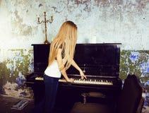 Recht junges blondes wirkliches Mädchen am Klavier verrosteten interi im im alten Stil Stockfotografie