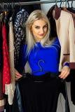 Recht junges erwachsenes blondes Mädchen choosig kleidet im Shop Stockbild