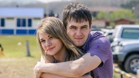 Recht junges glückliches Paar, das auf dem Strand umarmt stockbild