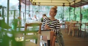 Recht junges kaukasisches Mädchen, das am Freiencafé sitzt und auf jemand wartet stock video