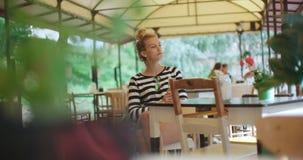 Recht junges kaukasisches Mädchen, das am Freiencafé sitzt und auf jemand wartet stock footage