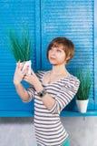 Recht junges kurzhaariges kaukasisches Mädchen, das pott hält? d-Anlage nahe blauem Fenster Atelieraufnahme, Gartenarbeitkonzept, lizenzfreies stockfoto