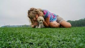 Recht junges Mädchen, das auf dem Gras mit ihrem Labrador-Welpen des dreimonatigen Babys liegt stockbild