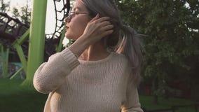 Recht junges Mädchen, das auf dem purpurroten Fechten in amusment Park, Liebkosungshaar sich lehnt stock footage
