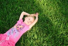 Recht junges Mädchen, das auf grünem Gras sich entspannt Stockfotografie