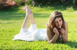 Recht junges Mädchen, das auf Gras mit bloßen Füßen liegt stockbilder