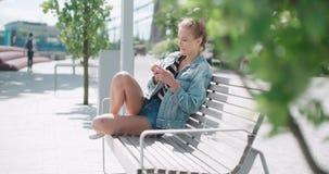 Recht junges Mädchen, das auf Holzbank unter Verwendung des Telefons sitzt stock video footage