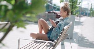 Recht junges Mädchen, das auf Holzbank unter Verwendung des Telefons sitzt stock footage