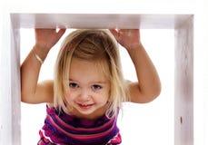 Recht junges Mädchen, das durch einen Kasten lächelt Lizenzfreie Stockfotos