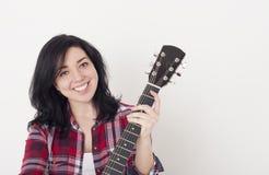 Recht junges Mädchen, das einen Akustikgitarrehals, die Kamera und das Lächeln betrachtend hält stockfotografie