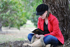 Recht junges Mädchen, das heilige Bibel unter großem Baum im Park liest Stockfotografie
