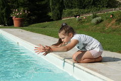 Recht junges Mädchen, das mit Wasser am Rand des Pools spielt lizenzfreie stockfotografie