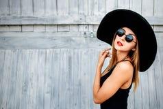 Recht junges Mädchen, das nahe hölzerner Wand in der schwarzen Badebekleidung steht Lizenzfreie Stockbilder