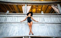 Recht junges Mädchen, das nahe hölzerner Wand in der schwarzen Badebekleidung steht Lizenzfreies Stockfoto