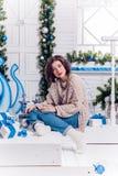 Recht junges Mädchen in den Jeans und eine Wolljacke auf der Veranda des neuen Jahres Stockfotos