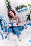 Recht junges Mädchen in den Jeans und eine Wolljacke mit Weihnachtsgeschenken c Stockfotos