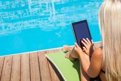 Recht junges Mädchen erhält Sonnenbräune nahe Wasser Stockfoto