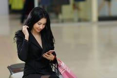 Recht junges Mädchen hält Einkaufstaschen und benutzt ein intelligentes Telefon im Mall Stockbilder