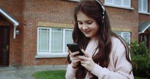 Recht junges Mädchen mit den Kopfhörern, die im Vorgarten des Hauses sitzen Simsende Mitteilung des Mädchens am Handy mit Landhau stock footage