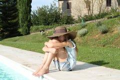 Recht junges Mädchen mit den Armen um Knie am Rand des Pools Stockfoto