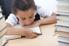 Recht junges Schule-Mädchen, das ein Buch liest Stockfoto