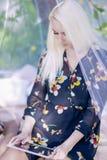 Recht kaukasische blonde Frau Ablesenebook draußen im Frühjahr Stockfoto