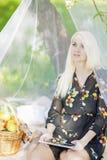 Recht kaukasische blonde Frau Ablesenebook draußen im Frühjahr Lizenzfreie Stockfotos