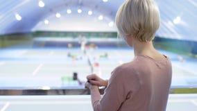 Recht kaukasische Frau beobachtet nach Tennisspielern vom Balkon am Gericht stock footage
