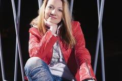 Recht kaukasische Frau in der roten Lederjacke und in den Blue Jeans, die draußen auf Straße nachts aufwerfen Stockbilder