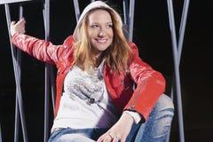 Recht kaukasische Frau in der roten Lederjacke und in den Blue Jeans, die im Hoodie aufwerfen Stockfotografie