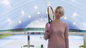 Recht kaukasische Frau mit Tennisschläger am Hintergrund von Tennisplätzen stock video
