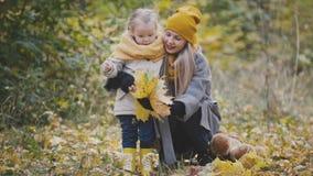 Recht kleine Tochter mit ihrer Mama spielt mit gelben Blättern im Herbstpark Lizenzfreie Stockfotografie