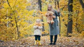 Recht kleine Tochter mit ihrer Mama spielt mit gelben Blättern im Herbstpark stockfotos