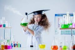 Recht kleiner Brunette, der im Chemielabor aufwirft Stockbilder