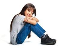 Recht kleines asiatisches Mädchen, das auf dem Boden sitzt Lizenzfreie Stockfotografie