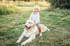Recht kleines Baby haben Spaß mit Hund Lizenzfreie Stockfotos