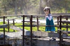 Recht kleines blondes langhaariges Mädchen im netten blauen Kleid steht Al Lizenzfreie Stockfotos